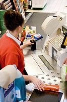 Cashier scanning purchases at checkout counter
