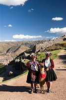 Inca women in traditional dress and llama, with the fortress of Sacsayhuaman in the background,, near Cuzco, Peru, South America
