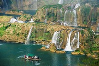 Tourist boats beneath Detian Falls, China and Vietnam transnational waterfall, Guangxi Province, China, Asia