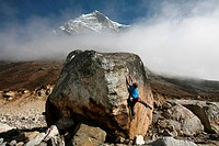 A climber tackles a difficult boulder problem on the glacial moraine at Tangnag, near Mera Peak and Mount Everest, Khumbu Region, Nepal, Himalayas, As...