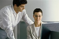 Young professional woman smiling, looking at computer screen while male colleague leans over her shoulder