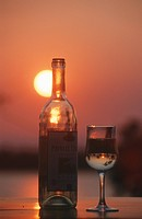 Wine glass and bottle against setting sun, Chete Island, Kariba, Zambia