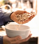 Pouring a Handful of Oats into a White Bowl