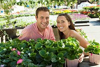 Young couple choosing potted flowers in garden centre portrait