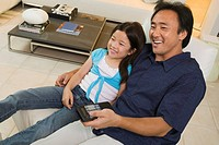 Father and Daughter Watching TV Together in living room high angle view