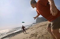 Two men playing with flying disc on beach