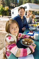Girl eating at picnic table with family in campground