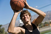 Young man shooting basketball portrait