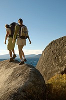 Couple hiking on boulders at coast