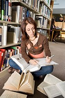Female college student making notes in library