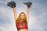 Cheerleader with pom poms raised portrait