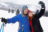 Couple on skis photographing selves using digital camera in snow covered field