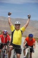 Cyclist cheering with raised arms portrait