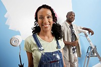 Couple holding paint rollers portrait