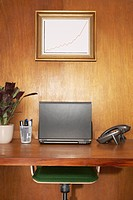Laptop and other items on desk framed graph above desk