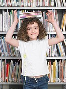 Girl balancing stack of books on head in library portrait