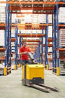 Mid_adult Man Driving Pallet Jack Through Warehouse