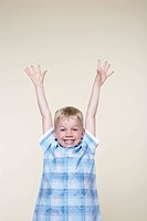 Smiling excited boy standing with Arms Raised