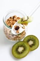 Yoghurt with muesli and kiwi fruit on spoon