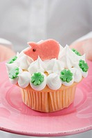 Hands holding cupcake with marzipan pig on pink plate