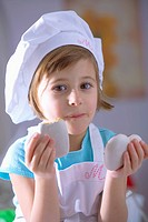Little girl in chef´s hat eating heart_shaped gingerbread