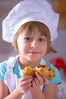 Little girl in chef´s hat holding raisin biscuits