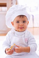 Little girl in chef´s hat eating biscuit