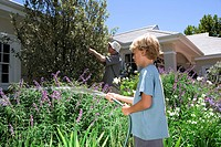Father and son 8_10 gardening, boy with hose, side view