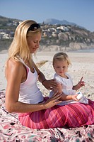 Mother applying sunscreen to baby girl 12_15 months on beach, side view