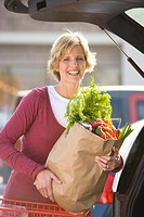 Woman loading grocery bags in car
