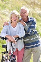 Portrait of senior couple leaning on bicycle