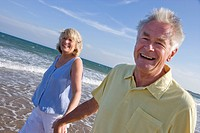 Portrait of senior couple walking on beach