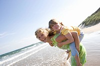 Portrait of mother piggybacking daughter on beach