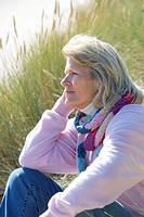Mature woman sitting on beach (thumbnail)