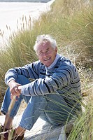 Portrait of senior man sitting on beach (thumbnail)
