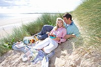 Portrait of young couple having picnic at beach