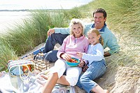 Portrait of young family having picnic at beach