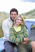 Portrait of young couple sitting on boat at beach