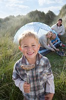 Young family camping, boy holding sausage