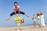 Young man leaping over friend at beach, women cheering