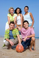 Portrait of young adults at beach with basketball