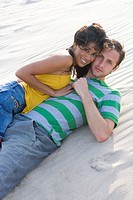 Young couple lying in sand at beach