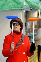 Woman in a red coat, fur hat and sunglasses spinning plates, Wales