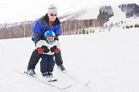 Grandfather teaching grandson to ski, Collingwood, Ontario