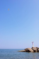 Man standing on breakwater flying a kite, Woodbine Beach, Toronto, Ontario