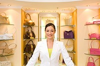 Saleswoman posing in front of purses