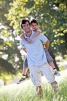 Father carrying son in field