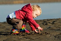 Toddler playing in wet sand by a pool on the beach, Wales