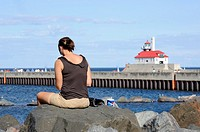 Woman ponders while sitting in harbor area of Duluth Minnesota
