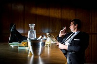 Vintage portrait of businessman relaxing with feet up and cigarette in boardroom